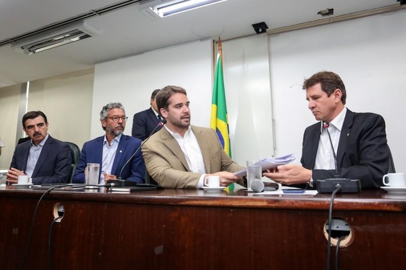 Governador Eduardo leite entrega um documento ao presidente da Assembleia legislativa. Ambos estão sentados atrás de uma mesa. À direita da foto vê-se outros dois homens sentados e um de pé.
