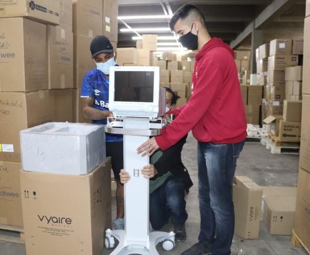 Funcionários do setor de suprimentos organizam os equipamentos