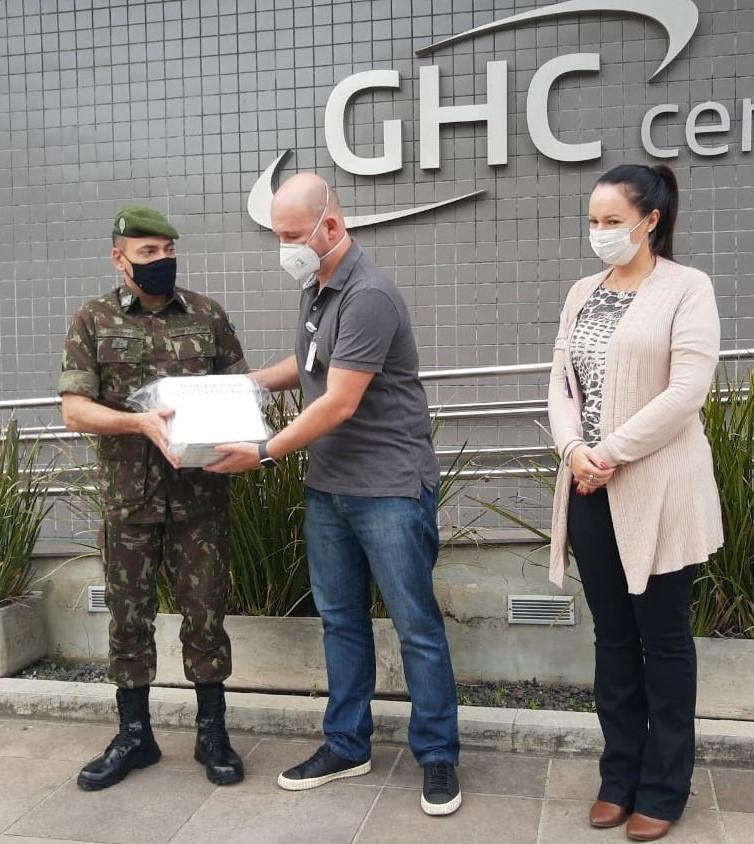 Um soldado do exército entrega medicamentos a representantes do Hospital Cristo Redentor recebe os medicamentos