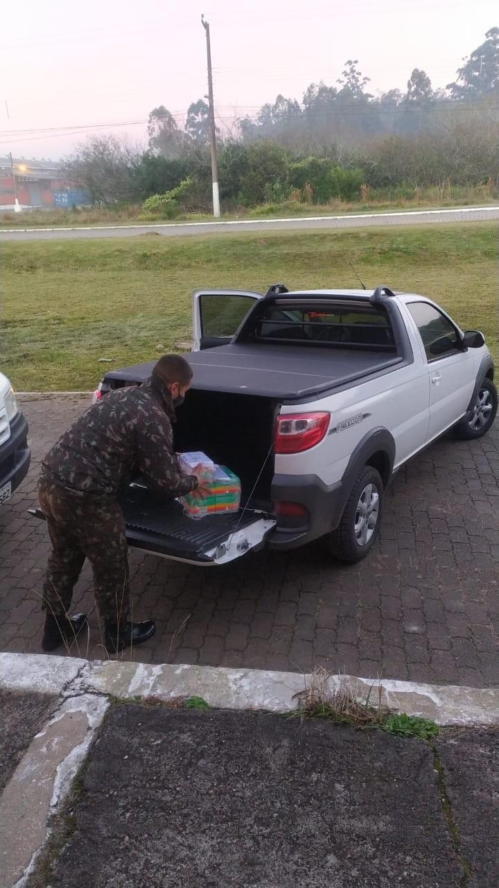 Militar coloca caixa com medicamentos no veiculo de transporte